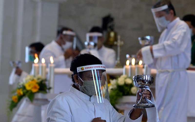 Petugas pemberi komuni yang mengenakan alat pelindung diri bersiap memberikan komuni kepada jemaat saat ibadah hari Minggu di Gereja Katolik Roh Kudus Katedral Denpasar, Bali, Minggu (5/7/2020). ANTARA FOTO/Fikri Yusuf