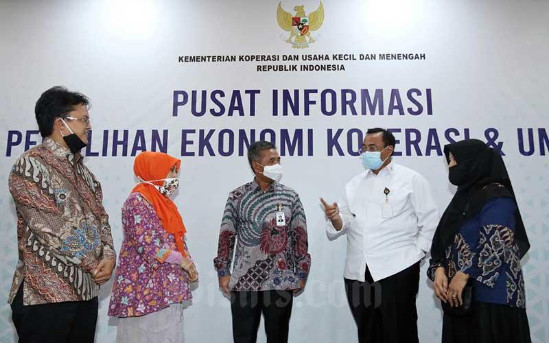 Sekretaris Kementerian Koperasi dan UKM Rully Indrawan (kedua kanan) bersama dengan Direktur Bisnis Mikro BRI Supari (tengah) berbincang dengan Penerima Manfaat KUR usai konferensi pers mengenai Program Pemulihan Ekonomi Nasional di Kantor Kementerian Koperasi dan UKM, Jakarta, Senin (6/7/2020). Dalam keterangan persnya, total anggaran dana Pemulihan Ekonomi Nasional (PEN) untuk UMKM sebesar Rp 123,46 triliun dan tidak semuanya dilaksanakan KemenkopUKM melainkan dikerjakan lintas Kementerian/Lembaga dan BUMN. Bisnis/Eusebio Chrysnamurti