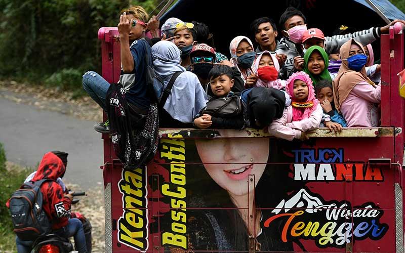Masyarakat Suku Tengger dengan mengenakan masker berada di atas truk menuju kawasan Gunung Bromo untuk melaksanakan perayaan Yadnya Kasada, Probolinggo, Jawa Timur, Senin (6/7/2020). Perayaan Yadnya Kasada merupakan bentuk ungkapan syukur masyarakat Suku Tengger dengan melarung sesaji berupa hasil bumi dan ternak ke kawah Gunung Bromo. ANTARA FOTO/Zabur Karuru
