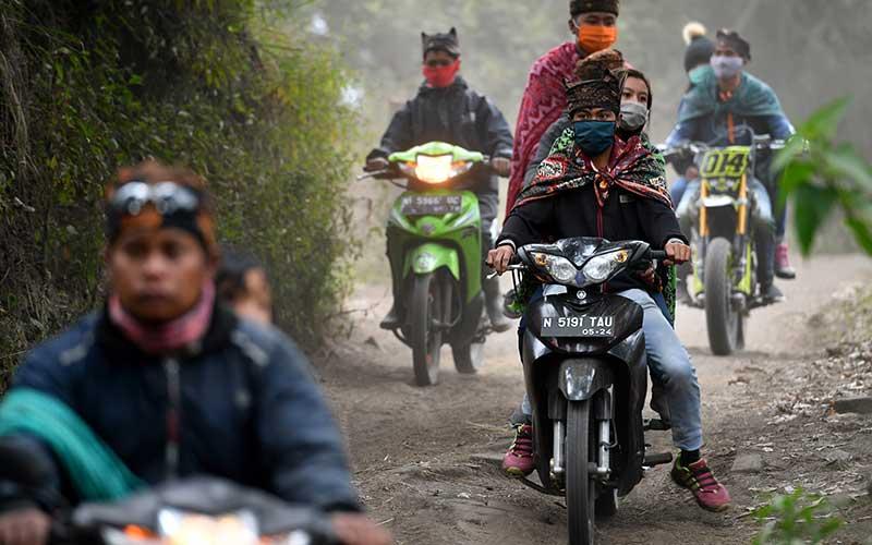 Masyarakat Suku Tengger dengan mengenakan masker melintas ketika menuju kawasan Gunung Bromo untuk melaksanakan perayaan Yadnya Kasada, Probolinggo, Jawa Timur, Senin (6/7/2020). Perayaan Yadnya Kasada merupakan bentuk ungkapan syukur masyarakat Suku Tengger dengan melarung sesaji berupa hasil bumi dan ternak ke kawah Gunung Bromo. ANTARA FOTO/Zabur Karuru