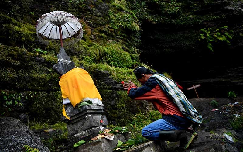 Masyarakat Suku Tengger berdoa sebelum mengambil air suci di Goa Widodaren di kawasan Gunung Bromo, Probolinggo, Jawa Timur, Senin (6/7/2020). Ritual berdoa dan ambil air suci tersebut merupakan rangkaian perayaan Yadnya Kasada bagi masyarakat Suku Tengger. ANTARA FOTO/Zabur Karuru