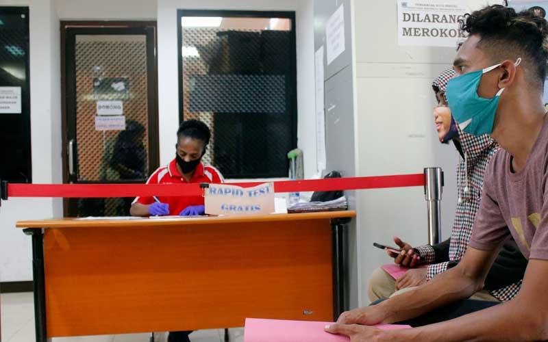 Warga (kanan) antre saat mengurus surat tanda rapit test gratis sebelum mengurus Surat Ijin Keluar Masuk (SIKM), di Posko Gugus Tugas Covid 19 Kota Sorong, Papua Barat, Selasa (7/7/2020). Tim gugus tugas Covid 19 Kota Sorong sejak dibukanya kembali transportasi massal pada awal Bulan Juni secara terbatas, telah mengeluarkan 3.000 lebih SIKM bagi masyarakat yang hendak datang ataupun meninggalkan Kota Sorong. ANTARA FOTO/Olha Mulalinda