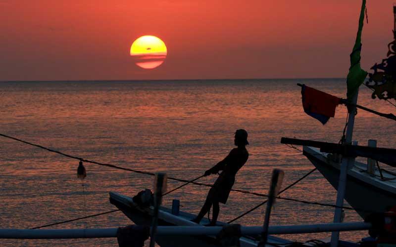 Nelayan beraktivitas diatas kapal saat matahari terbenam di dermaga Penarukan, Situbondo, Jawa Timur, Selasa (7/7/2020). Dermaga Penarukan yang difungsikan untuk bongkar muat hasil tangkapan nelayan dan angkutan barang ke kepulauan madura itu, juga ramai dikunjungi warga untuk melihat matahari terbenam. ANTARA FOTO/Budi Candra Setya