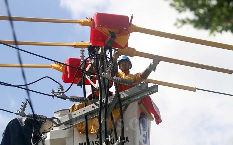Teknisi Pengerjaan Dalam Keadaan Bertegangan (PDKB) PLN mengerjalan perbaikan jaringan listrik kepelanggan di Makassar, Sulawesi Selatan, Rabu (8/7/2020). Pemerintah memutuskan untuk memperpanjang waktu pemberian bantuan keringanan biaya listrik kepada pelanggan PLN dengan daya 450 VA dan 900 VA bersubsidi hingga September 2020. Bisnis/Paulus Tandi Bone