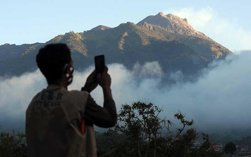 Seorang relawan mengabadikan video suasana Gunung Merapi yang terlihat dari kawasan Selo, Boyolali, Jawa Tengah, Rabu (8/7/2020). Bedasarkan data pengamatan Balai Penyelidikan dan Pengembangan Teknologi Kebencanaan Geologi (BPPTKG), pascaerupsi Gunung Merapi pada 21 Juni 2020 terjadi peningkatan deformasi atau perubahan tubuh Gunung Merapi sebesar 0,5 sentimeter per hari. ANTARA FOTO/Aloysius Jarot Nugroho