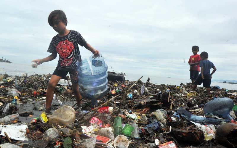 Anak-anak mengumpulkan barang bekas yang bisa dijual di antara timbunan sampah Pantai Muaro Lasak, Padang, Sumatera Barat, Kamis (9/7/2020). ANTARA FOTO/Iggoy el Fitra