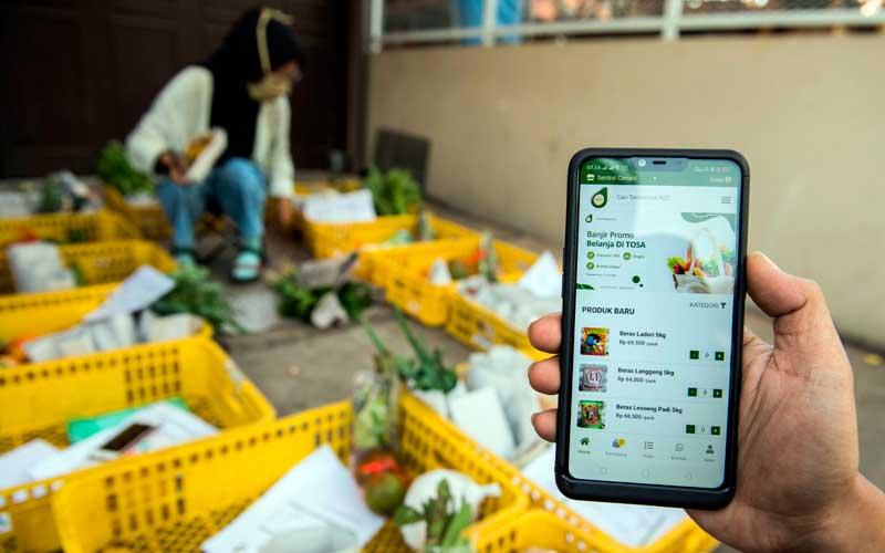 Pekerja menunjukan situs website belanja daring tokosampurna.com saat pengemasan komoditi pangan di kota Cimahi, Jawa Barat, Kamis (9/7/2020). ANTARA FOTO/M Agung Rajasa