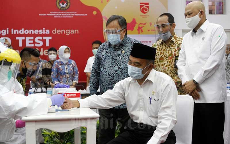 Menko PMK Muhadjir Effendi(depan duduk) disaksikan Menristek/BRIN Bambang PS Brodjonegoro (ketiga kanan), Kepala BPPT Hammam Riza (kanan) dan Kepala LKPP Roni Dwi Susanto (kedua kanan) melakukan rapid test di sela-sela konferensi pers di Jakarta, Kamis (9/7/2020). Bisnis/Himawan L Nugraha