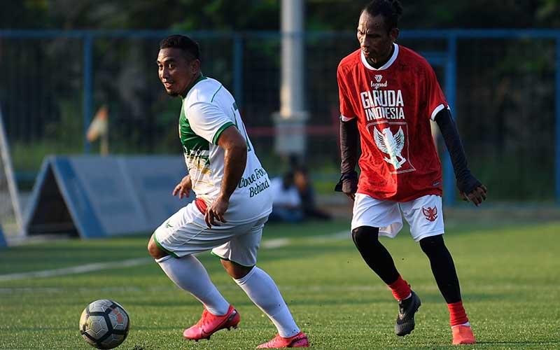 Pesepak bola Primavera-Baretti Indonesia Firman Utina (kiri) berebut bola dengan pesepak bola Garuda Indonesia Rochy Putiray (kanan) dalam pertandingan persahabatan di Jakarta, Sabtu (11/7/2020). ANTARA FOTO/Puspa Perwitasari