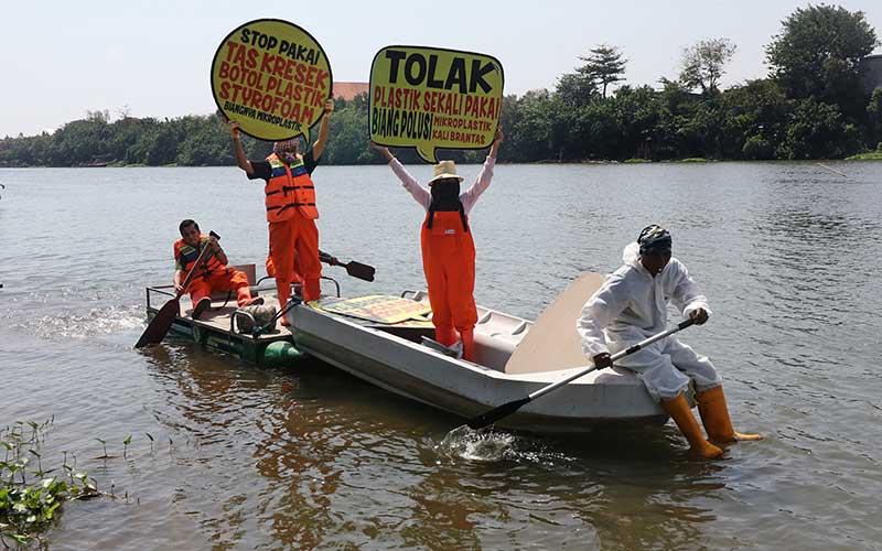 Aktivis lingkungan hidup dari Ecological Observation and Wetlands Conservation (Ecoton) membentangkan poster saat aksi tolak pencemaran sungai Brantas di Kota Kediri, Jawa Timur, Minggu (12/7/2020). ANTARA FOTO/Prasetia Fauzani
