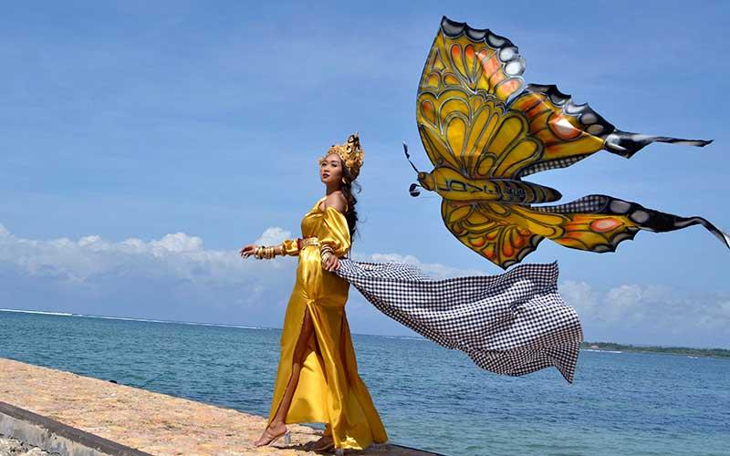 Model memperagakan busana bernuansa layang-layang disela-sela kegiatan Lomba Layangan Virtual di Sanur, Denpasar, Bali, Minggu (12/7/2020). ANTARA FOTO/Fikri Yusuf