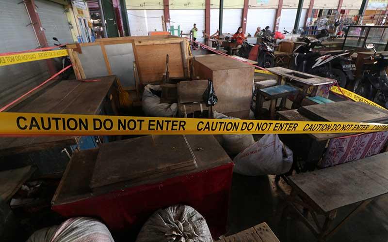 Garis pembatas masih terpasang di sejumlah lapak milik pedagang di Pasar Pahing, Kota Kediri, Jawa Timur, Senin (13/7/2020). Pemerintah kota setempat membuka kembali pasar tradisional itu setelah sebelumnya ditutup selama tiga hari pasca seorang pedagang dinyatakan positif Covid-19. ANTARA FOTO/Prasetia Fauzani