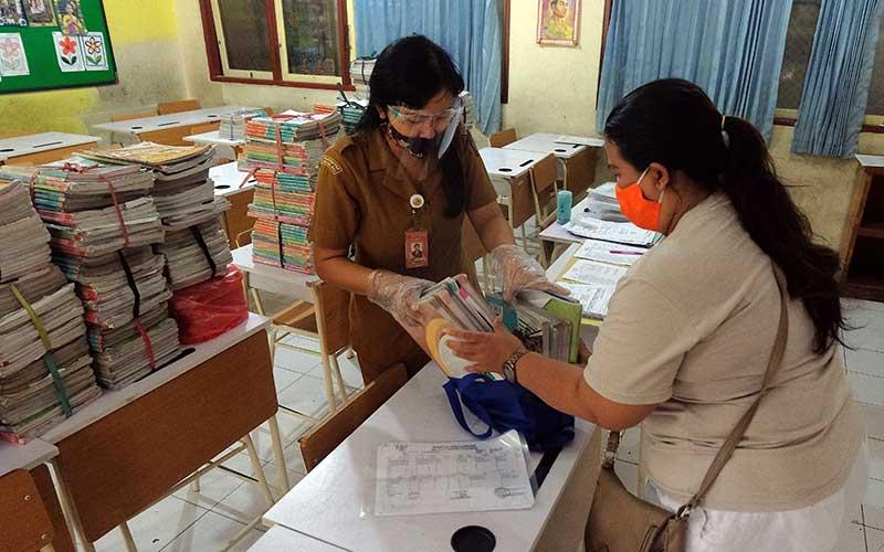 Seorang guru dengan masker dan pelindung di wajahnya melayani orang tua siswa yang mengembalikan buku dan pembagian buku baru pada hari pertama tahun ajaran baru di SD Negeri 17 Dauh Puri Denpasar, Bali, Senin (13/7/2020). ANTARA FOTO/Nyoman Hendra Wibowo
