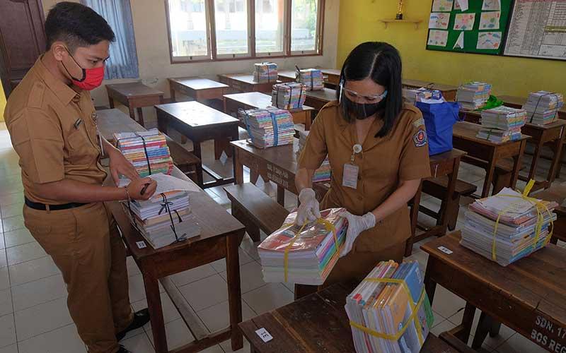 Dua guru memeriksa buku pelajaran yang akan dibagikan untuk siswa kelas VI pada hari pertama tahun ajaran baru di SD Negeri 17 Dauh Puri Denpasar, Bali, Senin (13/7/2020). ANTARA FOTO/Nyoman Hendra Wibowo