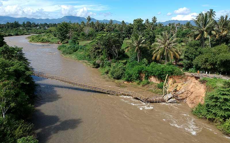 Foto udara jembatan gantung yang putus di Desa Bandungan, Kabupaten Bone Bolango, Gorontalo, Senin (13/7/2020). Jembatan yang dibangun pada tahun 2002 dan menjadi salah satu akses lintas Kecamatan Bulango Utara dan Tapa tersebut putus usai tergerus arus sungai pada Minggu (12/7) kemarin. ANTARA FOTO/Adiwinata Solihin