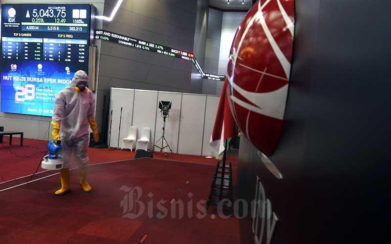 Petugas menyeprotkan disinfektan di main hall Bursa Efek Indonesia di Jakarta, Senin (13/7/2020). Bisnis/Abdurachman