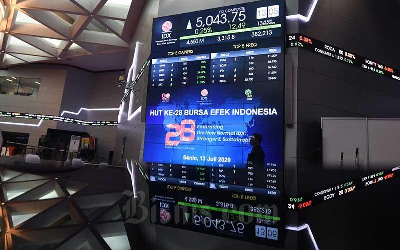 Petugas melintas di dekat papan elektronik yang menampilkan pergerakan Indeks Harga Saham Gabungandi main hall Bursa Efek Indonesia di Jakarta, Senin (13/7/2020). Bisnis/Abdurachman