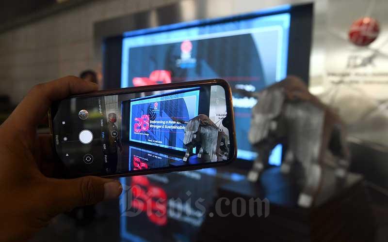 Karyawan menggunakan smart phone saat memotret logo Bursa Efek Indonesia di Jakarta, Senin (13/7/2020). Bisnis/Abdurachman