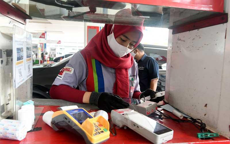 Petugas melakukan transaksi non tunai di stasiun pengisian bahan bakar umum (SPBU) di Jakarta, Senin (13/7/2020). Bisnis/Abdurachman
