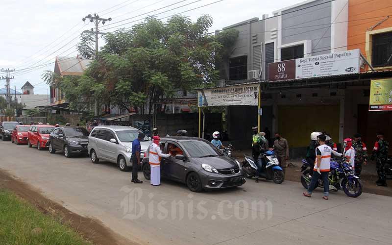 Petugas gabungan melakukan pemeriksaan surat bagi warga yang akan masuk ke kota Makassar di Barombong batas kabupaten Gowa dan kota Makassar, Senin (13/7/2020). Bisnis/Paulus Tandi Bone