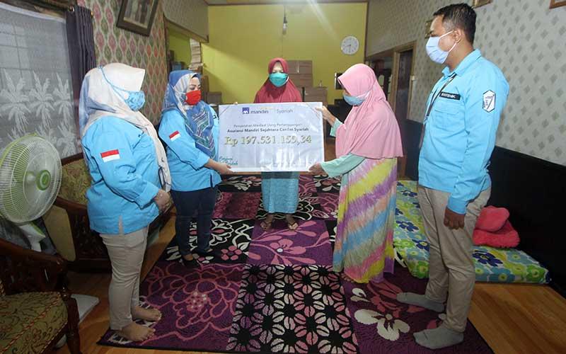 Perwakilan PT AXA Mandiri Financial Services (AXA Mandiri) Rini (dua kiri) menyerahkan pembayaran klaim asuransi jiwa secara simbolis kepada ahli waris nasabah AXA Mandiri Amaliah (dua kanan) di Banjarmasin, Kalimantan Selatan, Jumat (10/7/2020). Bisnis