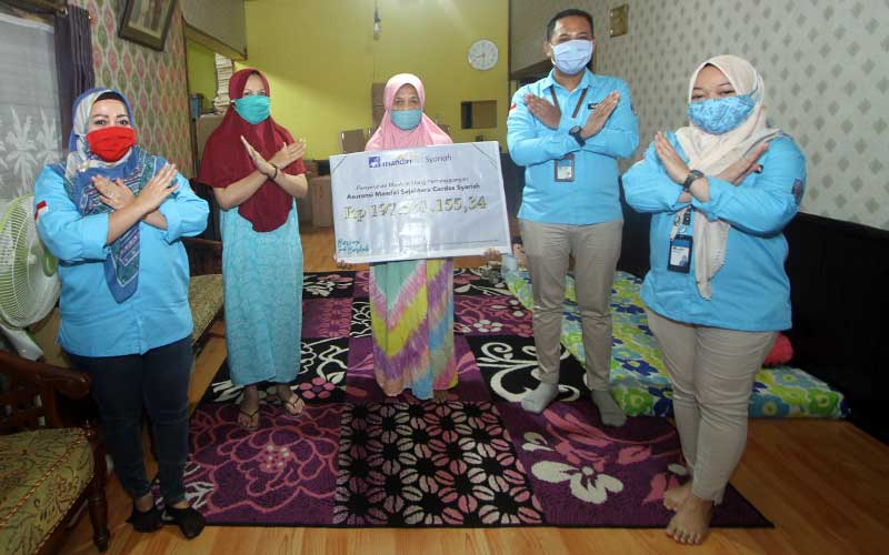 Perwakilan PT AXA Mandiri Financial Services (AXA Mandiri) Rini (dua kiri) berfoto bersama dengan ahli waris nasabah AXA Mandiri Amaliah (dua kanan) di sela-sela penyerahan pembayaran klaim asuransi jiwa secara simbolis kepada di Banjarmasin, Kalimantan Selatan, Jumat (10/7/2020). Bisnis
