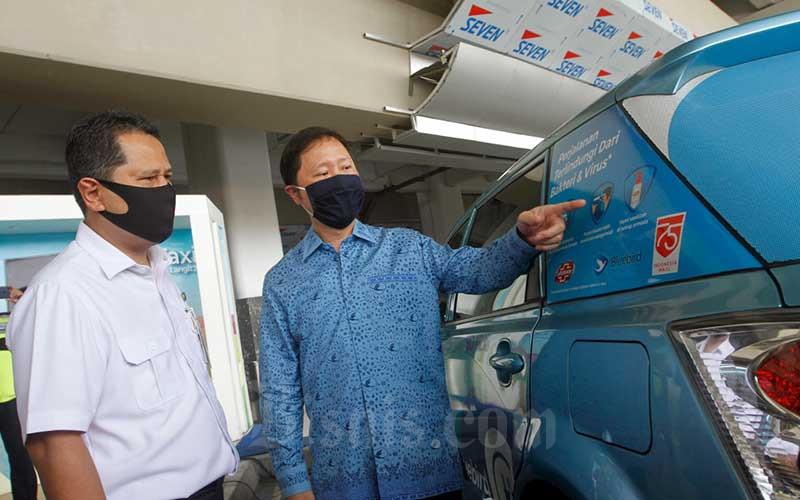 Direktur PT Blue Bird Tbk. Sigit Djokosoetono (kanan) dan Executive General Manager Kantor Cabang Utama Bandara Internasional Soekarno-Hatta PT Angkasa Pura II Agus Haryadi berbincang di dekat armada taksi Blue Bird dengan stiker higenis di Terminal 3 Bandara Soekarno-Hatta, Tangerang, Selasa (14/7/2020). Bisnis/Himawan L Nugraha