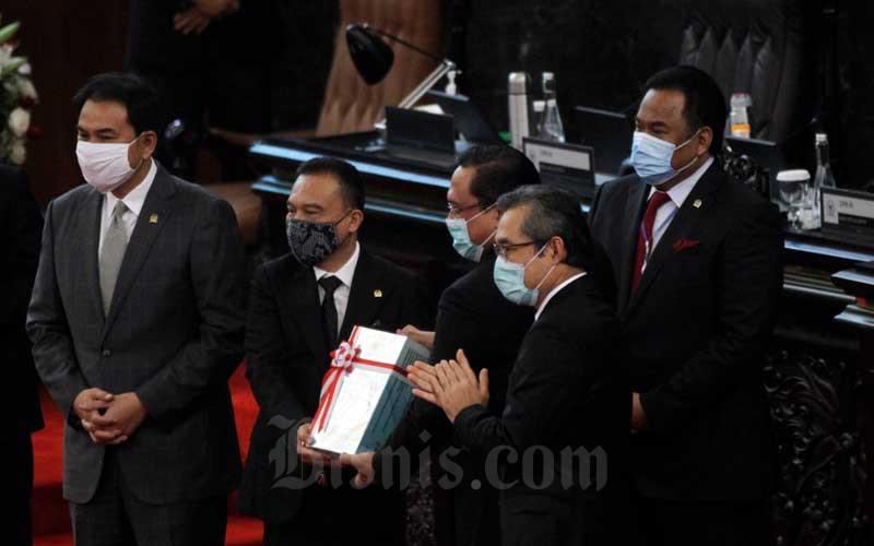 Ketua BPK Agung Firman Sampurna (tengah) didampingi Anggota I/Pimpinan Pemeriksaan Keuangan Negara I BPK Hendra Susanto (kedua kanan) menyerahkan hasil audit LKPP 2019 kepada Wakil Ketua DPR Sufmi Dasco Ahmad (kedua kiri) disaksikan Wakil Ketua DPR Aziz Syamsuddin (kiri) dan Wakil Ketua DPR Rachmad Gobel pada Rapat Paripurna DPR ke-18 Masa Persidangan IV Tahun 2019-2020 di Kompleks Parlemen, Jakarta, Selasa (14/7/2020). Bisnis/Himawan L Nugraha