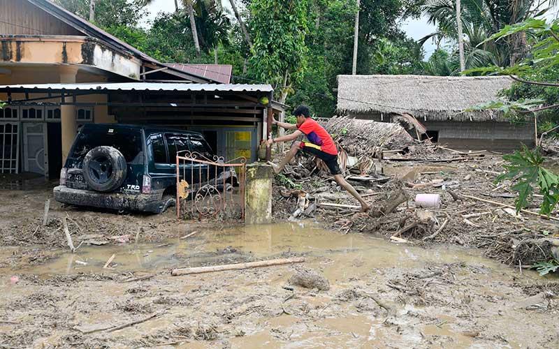 Warga berusaha memeanjat kedalam rumahnya yang tenggelam lumpur akibat banjir bandang di Desa Radda, Kabupaten Luwu Utara, Sulawesi Selatan, Selasa (14/7/2020). Akibat banjir bandang tersebut mengakibatkan 10 orang meninggal dunia dan ratusan rumah tertimbun lumpur. ANTARA FOTO/Hariandi Hafid