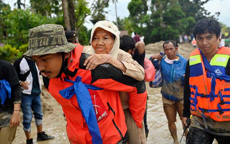 Tim SAR menggendong seorang korban banjir bandang saat dievakuasi di Desa Radda, Kabupaten Luwu Utara, Sulawesi Selatan, Selasa (14/7/2020). Akibat banjir bandang tersebut mengakibatkan 10 orang meninggal dunia dan ratusan rumah tertimbun lumpur. ANTARA FOTO/Hariandi Hafid