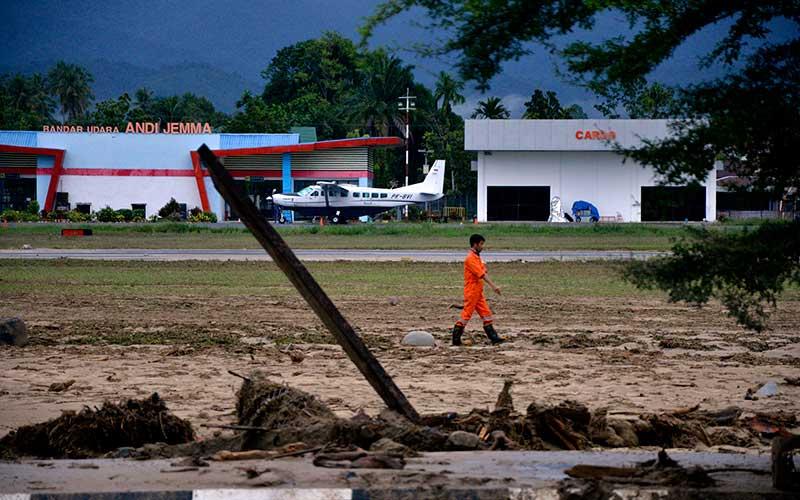 Petugas berjalan di area Bandar Udara Andi Djemma yang tertimbun lumpur akibat terjangan banjir bandang di Kecamatan Masammba, Kabupaten Luwu Utara, Sulawesi Selatan, Rabu (15/7/2020). ANTARA FOTO/Abriawan Abhe