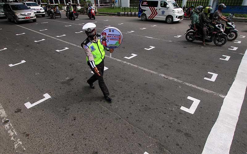 Polisi mengatur pengendara sepeda motor untuk berhenti di belakang garis untuk menjaga jarak antarpengendara saat sosialisasi penerapan jaga jarak di Kota Lhokseumawe, Aceh, Rabu (15/7/2020). Garis tersebut dibuat untuk membatasi jarak antarpengendara di kawasan traffic light guna mencegah penyebaran Covid-19. ANTARA FOTO/Rahmad