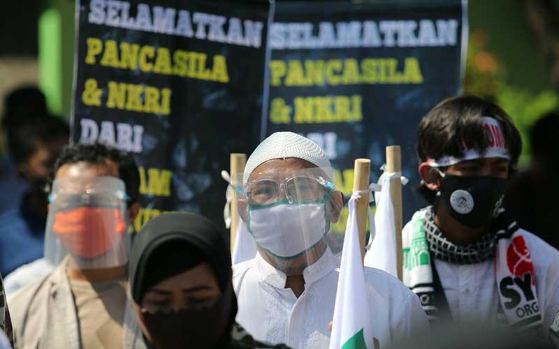 Warga yang tergabung dalam Pergerakan Umat Islam melakukan unjuk rasa bertajuk Aksi Penyelamatan Pancasila dari Komunisme dengan menerapkan protokol kesehatan di depan gedung DPRD Kota Kediri, Jawa Timur, Kamis (16/7/2020). ANTARA FOTO/Prasetia Fauzani