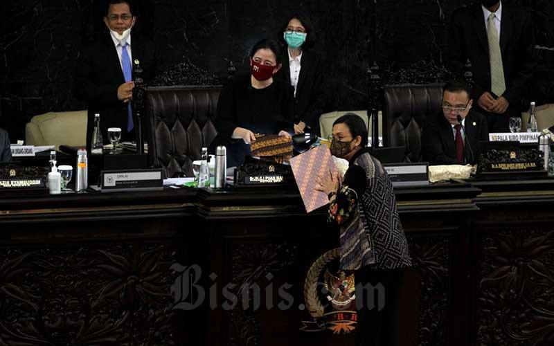 Menteri Keuangan Sri Mulyani Indrawati (kedua kanan) menyerahkan naskah kepada Ketua DPR Puan Maharani seusai memberikan pemaparan dalam rapat paripurna DPR di kompleks parlemen, Jakarta, Kamis (16/7/2020). Bisnis/Arief Hermawan P