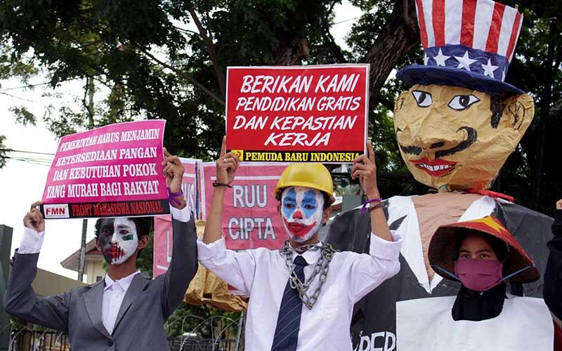 Demonstran membawa poster saat melakukan aksi unjuk rasa di depan Kantor DPRD Sulsel di Makassar, Sulawesi Selatan, Kamis (16/7/2020). Mereka menuntut DPR membatalkan Rancangan Undang-Undang (RUU) Omnibus Law Cipta Kerja serta mendesak pemerintah untuk menggratiskan biaya pendidikan di tengah pandemi COVID-19. ANTARA FOTO/Arnas Padda