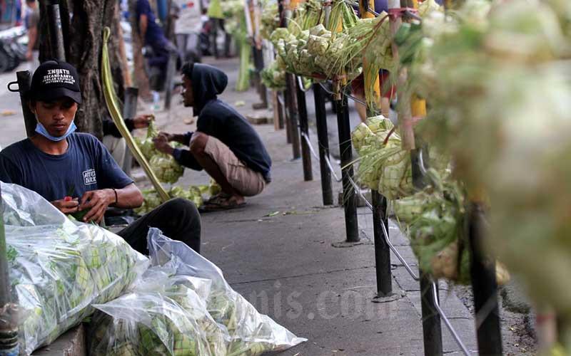 Pedagang kulit ketupat menunggu pembeli di sekitar pasar Pondok Labu, Jakarta, Kamis (30/7/2020). Pedagang disini mengaku alami penurunan omset hingga 50 persen dibandingkan dengan Idul Adha tahun lalu. Kulit ketupat terpaksa dijual Rp5-8 ribu per ikat, jauh dari harga pada tahun sebelumnya yang mencapai Rp20-25 ribu per ikat. Bisnis/Arief Hermawan P