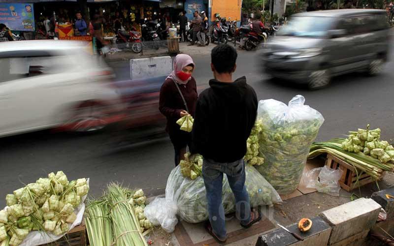 Pedagang kulit ketupat melayani pembeli di sekitar pasar Pondok Labu, Jakarta, Kamis (30/7/2020). Pedagang disini mengaku alami penurunan omset hingga 50 persen dibandingkan dengan Idul Adha tahun lalu. Kulit ketupat terpaksa dijual Rp5-8 ribu per ikat, jauh dari harga pada tahun sebelumnya yang mencapai Rp20-25 ribu per ikat. Bisnis/Arief Hermawan P