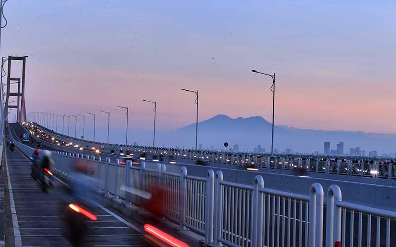 Pengendara motor melintasi Jembatan Suramadu di Bangkalan, Jawa Timur, Kamis (30/7/2020). Menjelang Hari Raya Idul Adha 1441 H, jembatan penghubung antara Pulau Jawa dengan Pulau Madura tersebut dipadati kendaraan khususnya pemudik yang menggunakan motor menuju Pulau Madura. ANTARA FOTO/Zabur Karuru