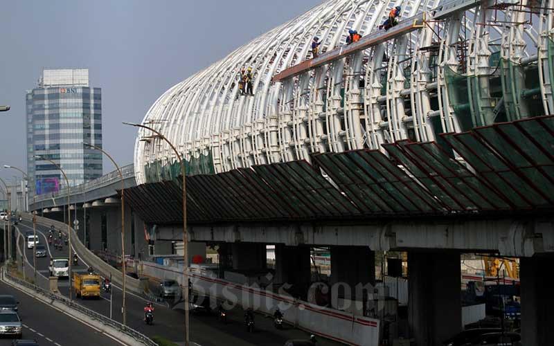 Pekerja beraktivitas menyelesaikan proyek pembangunan LRT di Jakarta, Minggu (2/8/2020). Pemerintah terus melanjutkan pembangunan infrastruktur di tengah pandemi Covid-19, pasalnya sektor konstruksi masih menjadi tumpuan utama pemerintah untuk menurunkan angka pengangguran. Bisnis/Arief Hermawan P