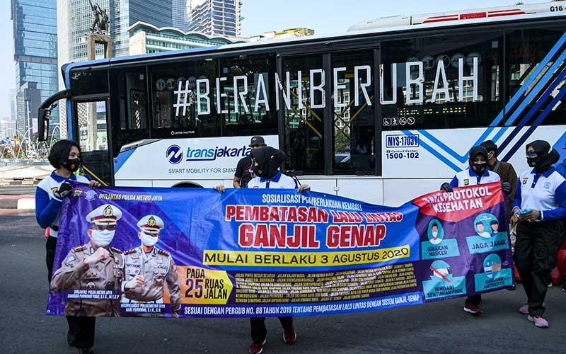Sejumlah anggota Kepolisian membentangkan spanduk sosialisasi pemberlakuan kembali ganjil genap di Bundaran Hotel Indonesia, Jakarta, Minggu (2/8/2020). Pemprov DKI Jakarta menerapkan kembali aturan ganjil genap bagi kendaraan roda empat saat masa PSBB transisi mulai Senin (3/8/2020) di 25 ruas jalan Ibu Kota. ANTARA FOTO/M Risyal Hidayat
