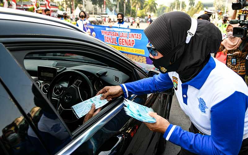Anggota Polisi wanita membagikan masker pada pengendara mobil saat sosialisasi pemberlakuan kembali ganjil genap di Bundaran Hotel Indonesia, Jakarta, Minggu (2/8/2020). Pemprov DKI Jakarta menerapkan kembali aturan ganjil genap bagi kendaraan roda empat saat masa PSBB transisi mulai Senin (3/8/2020) di 25 ruas jalan Ibu Kota. ANTARA FOTO/M Risyal Hidayat