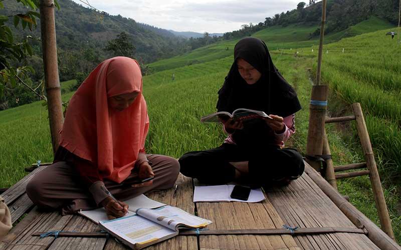 Sejumlah siswa SMA mengikuti kegiatan belajar daring di area persawahan Bassaran, Desa Rante Mario, Kabupaten Enrekang, Sulawesi Selatan, Senin (3/8/2020). Siswa di daerah tersebut terpaksa mencari tempat tinggi untuk mengikuti kegiatan belajar mengajar daring selama pandemi Covid-19 akibat sulitnya akses internet di daerah itu. ANTARA FOTO/Arnas Padda