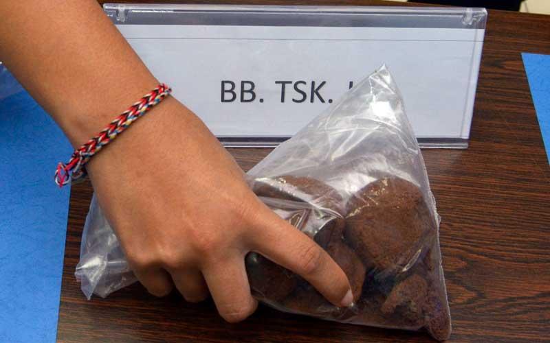 Petugas menunjukkan barang bukti kue mengandung ganja milik tersangka kasus narkotika asal Amerika Serikat berinisial JO saat rilis di Kantor Badan Narkotika Nasional (BNN) Provinsi Bali, Denpasar, Bali, Selasa (4/8/2020). JO yang merupakan mahasiswa magang di salah satu lembaga sosial di Bali ditangkap setelah menerima paket pos berisi kue yang mengandung narkotika jenis ganja dengan berat 130 gram yang dikirimkan dari Puerto Rico. ANTARA FOTO/Fikri Yusuf