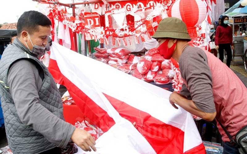 Pedagang bendera dan pernak-pernik kemerdekaan melayani pembeli di Pasar Jatinegara, Jakarta, Selasa (4/8/2020). Menjelang Hari Ulang Tahun (HUT) Kemerdekaan Indonesia ke-75 penjual bendera dan pernak-pernik kemerdekaan mengaku bahwa omzet mereka turun hingga 50 persen akibat adanya pandemi Covid-19.Bisnis/Himawan L Nugrahan