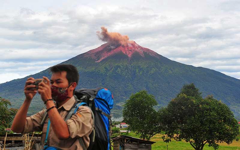 Warga mengamati suasana perkampungan saat Gunung Kerinci mengembuskan gas dan material yang terlihat dari Gunung Tujuh, Kerinci, Jambi, Rabu (5/8/2020). Pos Pengamatan Gunung Api Kerinci menyebutkan Gunung Kerinci yang statusnya masih berada pada level II (waspada) kembali mengalami gempa embusan dan tremor menerus yang terpantau secara visual dan data seismik pada Rabu (5/8) pagi. ANTARA FOTO/Wahdi Septiawan