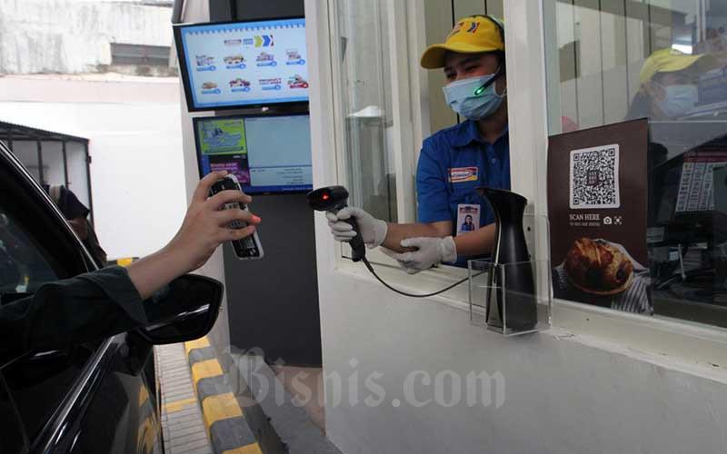 Konsumen melakukan pembayaran saat berbelanja melalui layanan Indomaret Drive Thru di Jakarta, Rabu (5/8/2020). Indomaret melakukan ekspansi usaha dengan menambah layanan drive thru keempatnya menyusul keberhasilan layanan sejenis sebelumnya. Bisnis/Dedi Gunawann