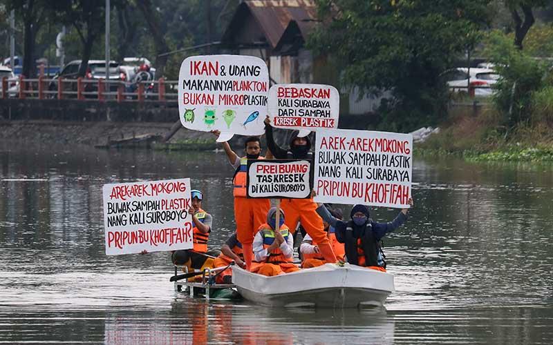Sejumlah aktivis lingkungan yang tergabung dalam Ecoton membentangkan poster diatas perahu di Sungai Surabaya, Jawa Timur, Rabu (5/8/2020). Aksi itu guna menyadarkan masyarakat agar tidak membuang sampah khususnya sampah plastik ke sungai yang berakibat membahayakan kehidupan biota sungai. ANTARA FOTO/Didik Suhartono