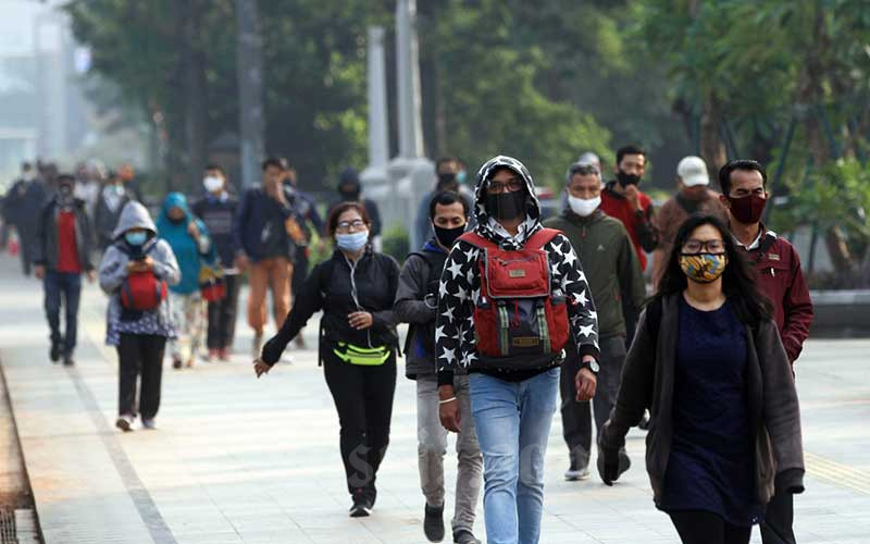 Karyawan berjalan menuju kantor mereka di kawasan Sudirman, Jakarta, Kamis (6/8/2020). Pemerintah menyampaikan akan memberi bantuan bagi karyawan swasta dengan gaji di bawah Rp5 juta dan setiap karyawan nantinya akan mendapat bantuan Rp600.000 per bulan selama empat bulan. Bisnis/Himawan L Nugraha