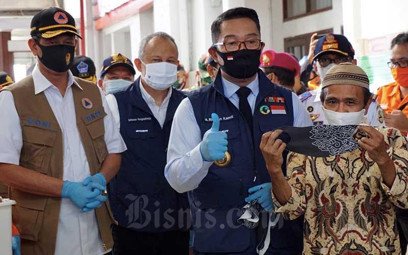 Kepala Satuan Tugas Nasional Penanganan Covid-19 Doni Monardo (kiri) bersama Gubernur Jawa Barat Ridwan Kamil (ketiga kiri) membagikan masker ke calon penumpang kereta api di Stasiun Bandung, Bandung, Jawa Barat, Kamis (6/8/2020). Bisnis/Rachman