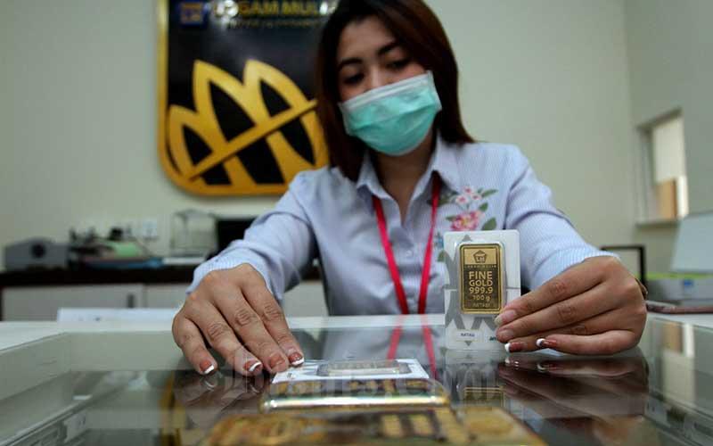 Karyawati menunjukkan replika logam mulia di Butik Emas Antam, Jakarta, Kamis (6/8/2020). Berdasarkan informasi Unit Bisnis Pengolahan dan Pemurnian Logam Mulia Antam, harga emas Antam ukuran 1 gram naik Rp6.000 ke posisi Rp1.054.000 pada perdagangan Kamis (6/8). Bisnis/Arief Hermawan P